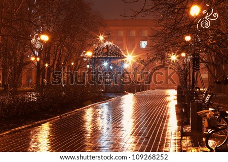 Scenic view of empty night alley in the city park in rain - stock photo