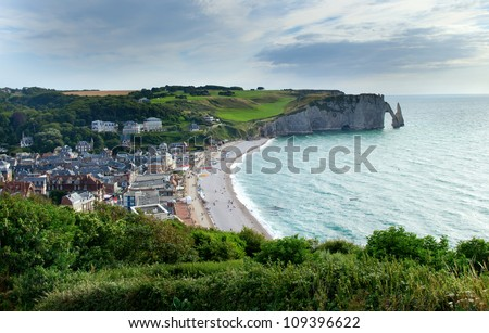 Scenic view of Etretat town with its beach and famous cliffs with arches