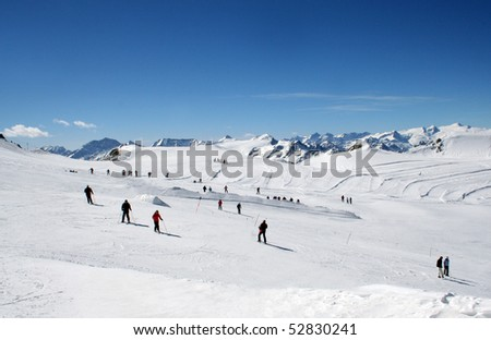 Scenic view of group of skiers on Alpine ski slope with blue sky background. - stock photo
