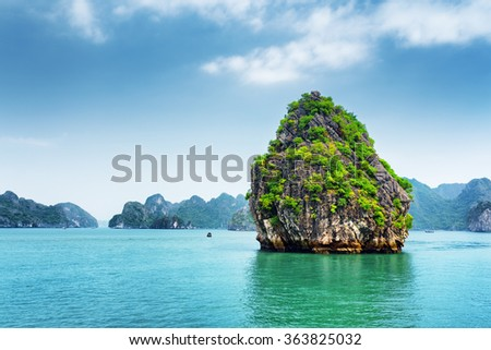 Scenic view of karst isle on blue sky background in the Ha Long Bay (Descending Dragon) at the Gulf of Tonkin of the South China Sea, Vietnam. The Halong Bay is a popular tourist destination of Asia. - stock photo