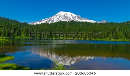 Scenic view of Mount Rainier reflected across the reflection lakes on a clear day - stock photo