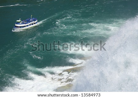 Scenic view of Niagara falls with boat full of tourists - stock photo