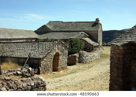 Scenic view of old stone farmhouse in countryside under blue sky, Lozere, France. - stock photo
