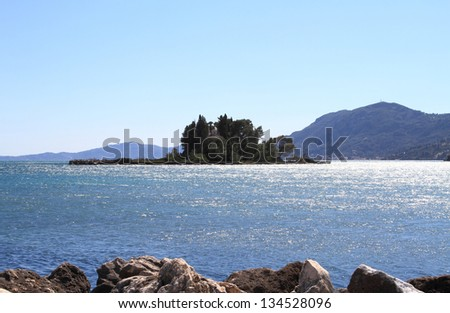 Scenic view of pontikonisi island behind the rocks - stock photo