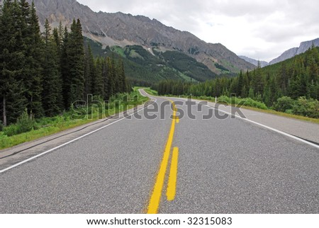 Scenic view of rocky mountains and highway 40 while traveling in kananaskis country, alberta, canada - stock photo