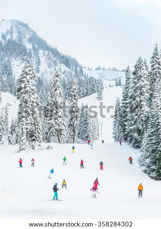 scenic view of small people around ski resort when sunset in snowy day. - stock photo