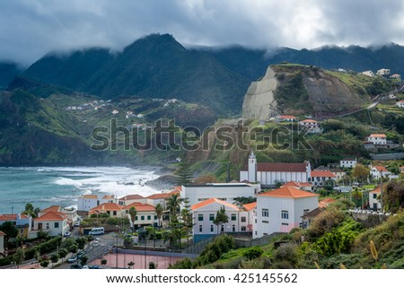 Scenic view of small touristic town Porto da Cruz, surrounded by volcanic rocks and mountains on the north shore of Madeira island, Portugal.