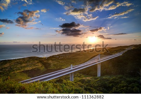 Scenic view of sunset and cloudscape over Trois Bassins viaduct on Reunion Island. - stock photo