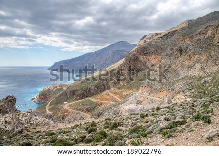 Scenic view of the coastline on Crete, Greece showing a road winding down the steep mountainside to the shoreline below - stock photo