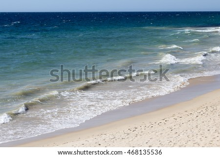 Scenic view of  the  Indian Ocean waves breaking onto the sandy shore  at  Ocean Beach Bunbury Western Australia on a fine hot  morning in summer is fascinating to watch.