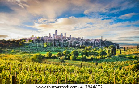 Scenic view of the medieval town of San Gimignano in beautiful scenery with vineyards in beautiful golden evening light with blue sky and clouds at sunset in summer, Tuscany, province of Siena, Italy - stock photo