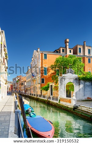 Scenic view of the Rio Marin Canal and colorful facades of medieval houses in Venice, Italy. The Ponte Cappello dei Garzoti is visible in background. Venice is a popular tourist destination of Europe. - stock photo