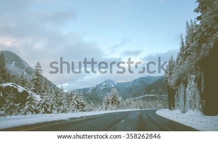scenic view of the road with snow and mountain background in winter season ,vintage style.