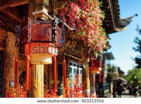 Scenic view of traditional Chinese street lanterns and pink flowers on facade of house in the Old Town of Lijiang, Yunnan province, China. Curved roof on blue sky background. Focus on the lantern. - stock photo