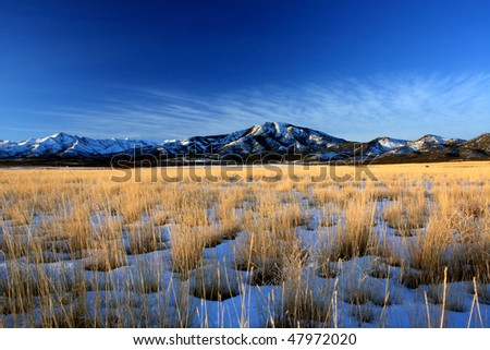 Scenic view of Utah desert in winter with snow capped mountain range in background