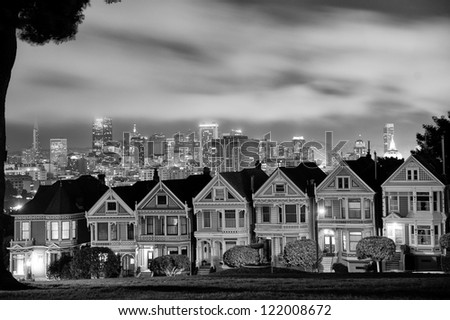 Scenic view of Victorian homes on Steiner Street at night with San Francisco city skyline in background viewed from Alamo Square Park, California, U.S.A.