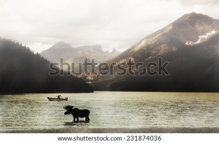 Scenic view of Waterton Lakes National Park at a foggy morning with moose silhouetted in foreground, Alberta, Canada. - stock photo