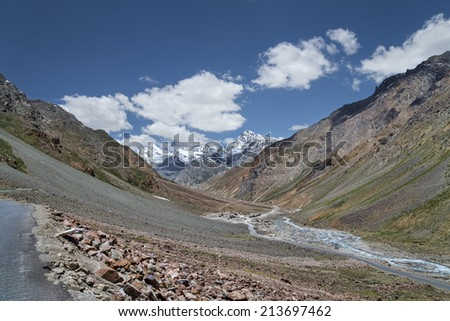 Scenic view of winding mountain road among snowy mountains - stock photo