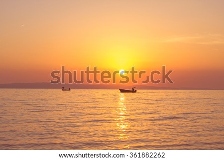 Scenic view on beautiful sunset above sea, with fishermen boats on water.