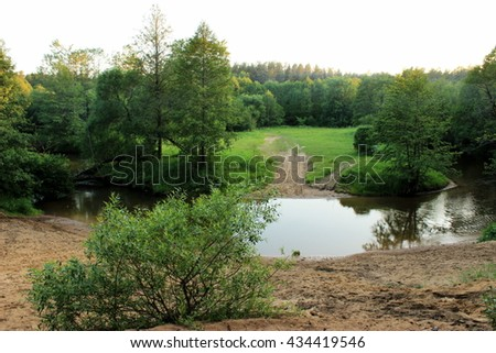 Scenic view on small river in a lush, forbidden environment / Tranquil river flowing in a lush summer forest. reflection of plants in a water - stock photo