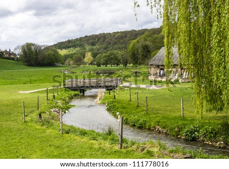 Scenic view on the french spring countryside with river and bridge - stock photo