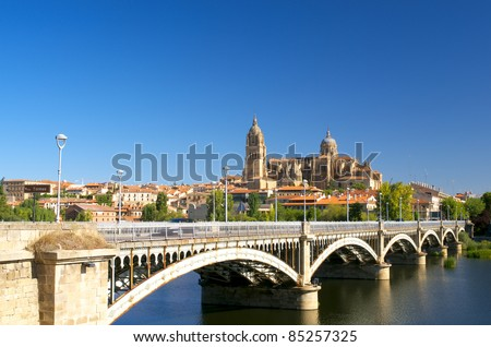 Scenic view to Salamanca Cathedral with bridge over Tormes river - stock photo