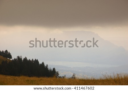 Scenic view with silhouettes of Alps mountains and a valley in gloomy autumn evening. Annecy lake area (Haute-Savoie, France). - stock photo
