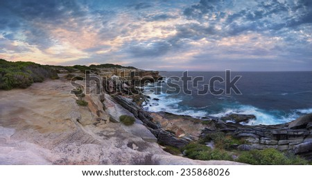 Scenic views north at Cape Solander.  Sydney Australia.  You would not want to have been standing on the cliff ledges when it gave way and crumbled onto the lower rock shelf and ocean - stock photo