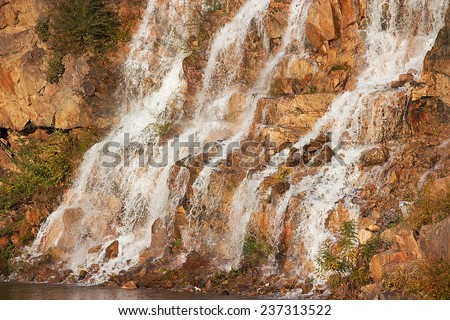 Scenic waterfall with white water cascading over yellow rock - stock photo