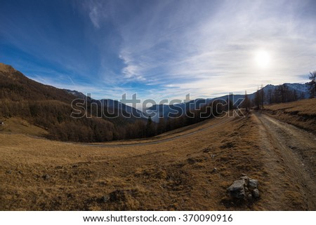 Scenic winding dirt road climbing valley to mountain pass with moody sky and great views. Captured in backlight by ultrawide angle fisheye lens in the Italian Alps. - stock photo