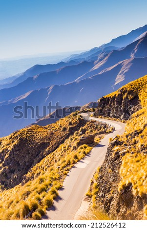 Scenic winding road on cliffs of mountain range at dawn. Beautiful colors. - stock photo