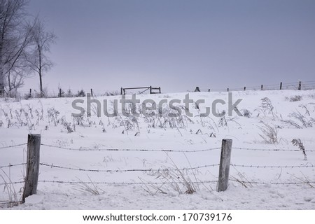 Scenic winter farm landscape with barbed wire fence in the foreground.  Hoarfrost clings to wire and trees.  Winter in Wisconsin - stock photo