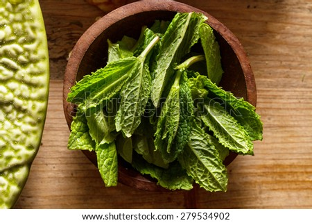 Scent of ingredients: mint leaves in wooden bowl on rustic wooden background. - stock photo