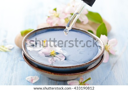 Scented oil and spring flowers for spa and aromatherapy on wooden table. - stock photo