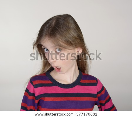 sceptical little girl against grey background