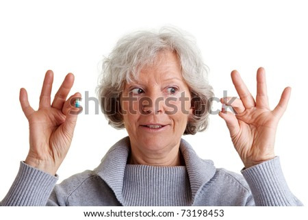 Sceptical old woman comparing two pills in her hands