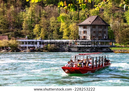 SCHAFFHAUSEN -APR 10: tourists at Rheinfall observation boat on April 10th, 2011 in Schaffhausen. Switzerland. Rheinfall is the biggest waterfall in Europe located on Switzerland and Germany border. - stock photo
