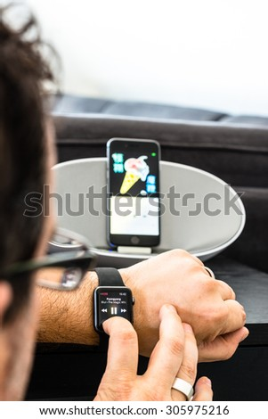 SCHARNHAUSEN, GERMANY - AUGUST 08, 2015: A man is controlling the playback of his Apple Music by using his Apple Watch to control his iPhone that is placed in a dock with loudspeakers in the - stock photo