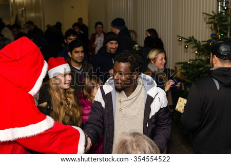 SCHARNHAUSEN, GERMANY - DECEMBER 20, 2015:: Refugees from Libya, Nigeria, Afghanistan, Pakistan, Eritrea, Gambia, Togo, Algeria, Tunisia and other countries are receiving presents from Santa Claus - stock photo