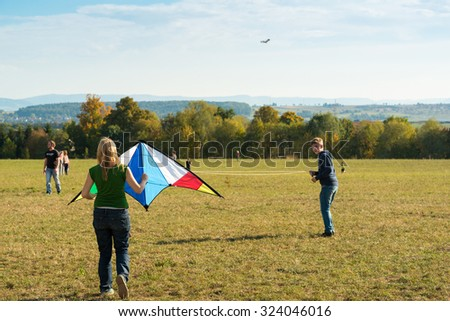 SCHARNHAUSEN, GERMANY - OCTOBER 3, 2015: Families are enjoying the great autumn weather by flying kites on a meadow during a sunny autumn day. - stock photo