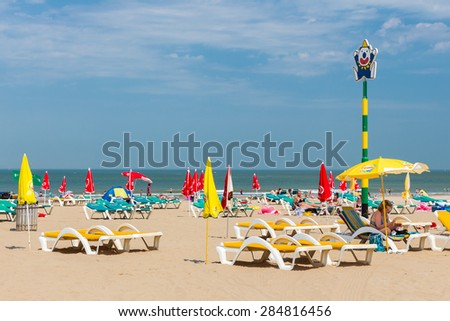 SCHEVENINGEN, THE NETHERLANDS - JUN 05: Seaside visitors relaxing in beach chairs at the first hot summerday on June 5, 2015 at the beach of Scheveningen, the Netherlands - stock photo