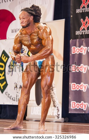 SCHIEDAM, THE NETHERLANDS - APRIL 26, 2015. Male bodybuilder Grego Francisca shows his best most muscular pose at the 38th Dutch National Championship Bodybuilding and Fitness