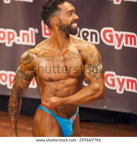 SCHIEDAM, THE NETHERLANDS - APRIL 26, 2015: Male bodybuilder showing his best at the 38th Dutch National Championship Bodybuilding and Fitness of the IFBB Netherlands (NBBF).