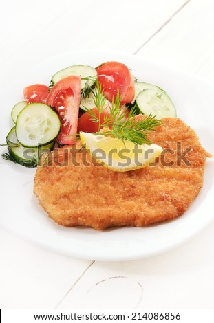 Schnitzel and salad with fresh vegetables on white plate - stock photo