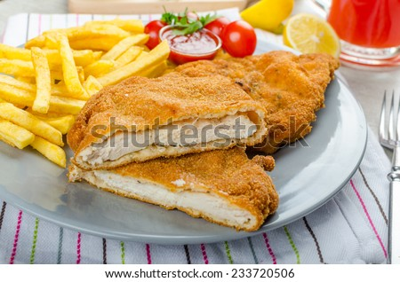 Schnitzel with french fries and a spicy dip, fresh from red orange - stock photo