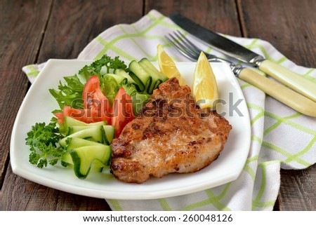 Schnitzel with vegetables on a plate, napkin and cutlery on a wooden background. Selective focus - stock photo