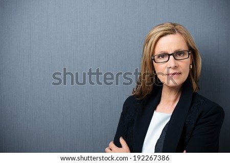 Scholarly looking middle-aged woman wearing heavy rimmed glasses and a black jacket standing with folded arms looking at the camera with a serious expression - stock photo
