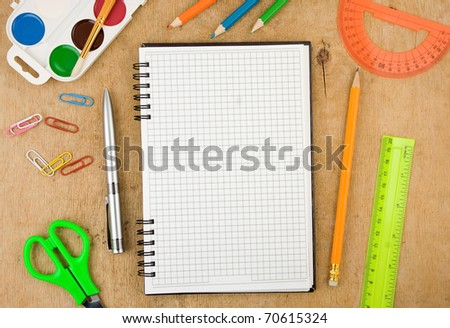 school accessories and checked notebook on wooden table