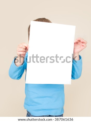 School age child holding a sign, blank page, picture, with copyspace. Education and learning concept