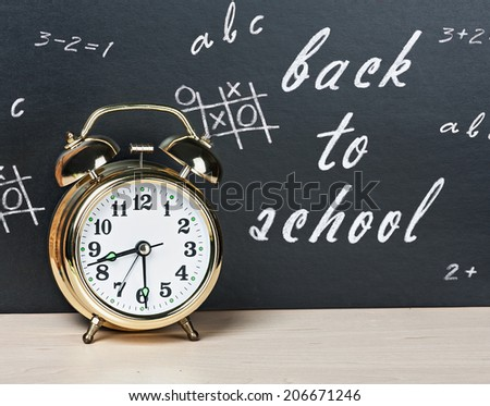 school alarm clock on a background of chalkboard